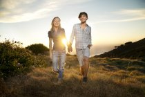Young couple walking hand in hand at the coast — Stock Photo