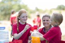 Kinder und Frau verteilen Erfrischungsgetränke — Stockfoto