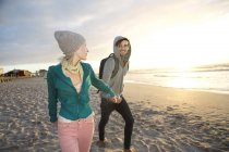 Young couple walking on beach at sunrise — Stock Photo
