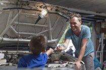 Син, допомагаючи батька в гараж працює над автомобіля — стокове фото