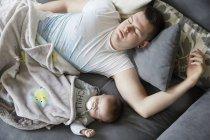 Молодий тато і дитини спати на дивані — стокове фото
