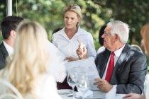 Waitress explaining menu to clients at table — Stock Photo