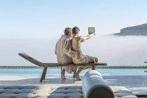 Couple gay au bord de la piscine en tenant un selfie avec tablette numérique — Photo de stock