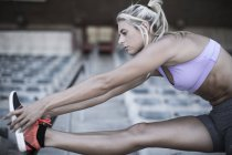 Sportswoman doing stretching exercies on grandstand of a stadium — Stock Photo
