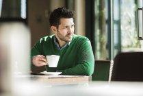 Uomo che beve caffè nel caffè e distoglie lo sguardo — Foto stock