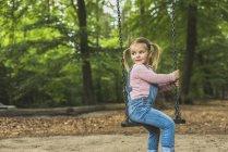 Smiling girl sitting on swing — Stock Photo