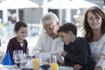 Grandfather and grandsons using digital tablet at family celebration — Stock Photo