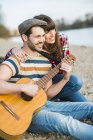 Couple sitting by the riverside, playing guitar — Stock Photo