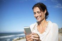 Портрет женщины улыбаясь, глядя на смартфон напротив моря — стоковое фото
