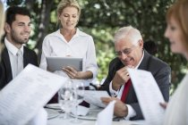 Camarera, teniendo a clientes pedidos de comida en la mesa utilizando una tableta digital - foto de stock