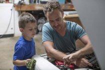 Filho, ajudando o pai na garagem em casa trabalhando no carro — Fotografia de Stock