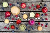 Différents smoothies aux fruits et fruits en bouteilles et en verre sur bois gris — Photo de stock