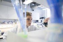 Jeune femme scientifique travaillant au laboratoire biologique — Photo de stock