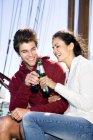 Щасливі молодий чоловік і жінка дзвінкою пивних пляшок на парусного корабля — стокове фото