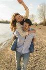 Людина, даючи piggyback їздити подругу в Ріверсайд — стокове фото