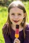 Дівчинка тримає паличці а облизуючи губи — стокове фото