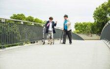 Senior couple with walking stick and wheeled walker on a bridge — Stock Photo