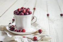 Свіжі Журавлина в чашки кави з тканиною на білий дерев'яний стіл — стокове фото