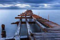 Chile, Punta Arenas, broken old jetty at sunset under clouds — Stock Photo