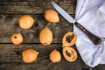 Sliced and whole medlars and kitchen knife on wooden surface — Stock Photo