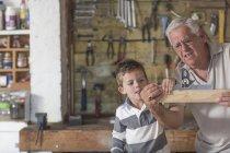 Grand-père et son petit-fils travaillant avec du bois dans un garage — Photo de stock