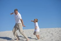 Playful father and son in sand on beach — Stock Photo
