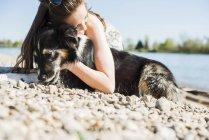 Jeune femme câlinant avec chien au Rhin, Allemagne, Mannheim — Photo de stock