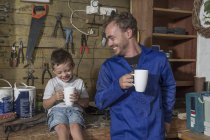 Father and son working in home garage having coffee break — Stock Photo