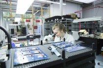 Técnico examinar circuitos con microscopio - foto de stock