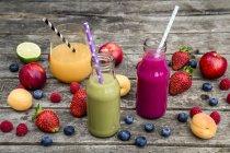 Nectars de fruits différents et des fruits frais sur une surface en bois grise — Photo de stock
