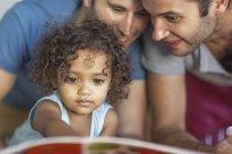 Zwei Männer mit Kind schauen sich Buch an — Stockfoto