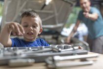 Son helping father in home garage working on car — Stock Photo