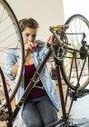 Jeune femme à la maison réparer son vélo — Photo de stock