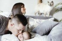 Jeune famille avec chat dans le salon — Photo de stock