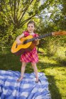 Girl playing guitar in garden — Stock Photo