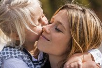 Girl hugging and kissing smiling mother — Stock Photo