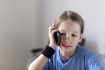Retrato de menino telefonando com smartphone em casa — Fotografia de Stock