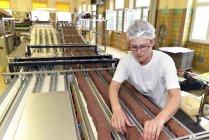Mujer que trabaja en la línea de producción en una fábrica para hornear - foto de stock