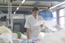 Worker in laundry looking at note — Stock Photo