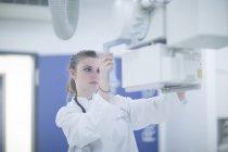 Jeune médecin s'adaptant à l'unité de radiographie à l'hôpital — Photo de stock