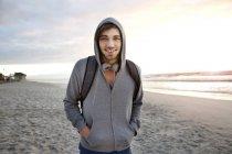 Улыбающийся молодой человек на пляже на рассвете — стоковое фото