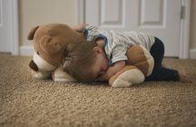 Tired little boy sleeping on the floor with bear — Stock Photo