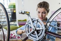 Young woman at home repairing her bicycle — Stock Photo