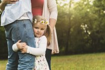 Girl embracing father's leg on meadow — Stock Photo