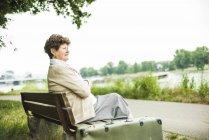 Старший женщина, сидя на скамейке — стоковое фото