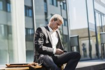 Businessman using mobile phone outdoors — Stock Photo