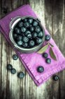 Arándanos en recipiente de zinc en madera oscura con la servilleta rosa - foto de stock