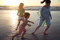 Семья, играя на пляже на закате — стоковое фото