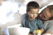 Close-up de pai e filho fazendo bolo — Fotografia de Stock