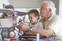 Nonno e nipoti costruiscono un aeroplano modello — Foto stock